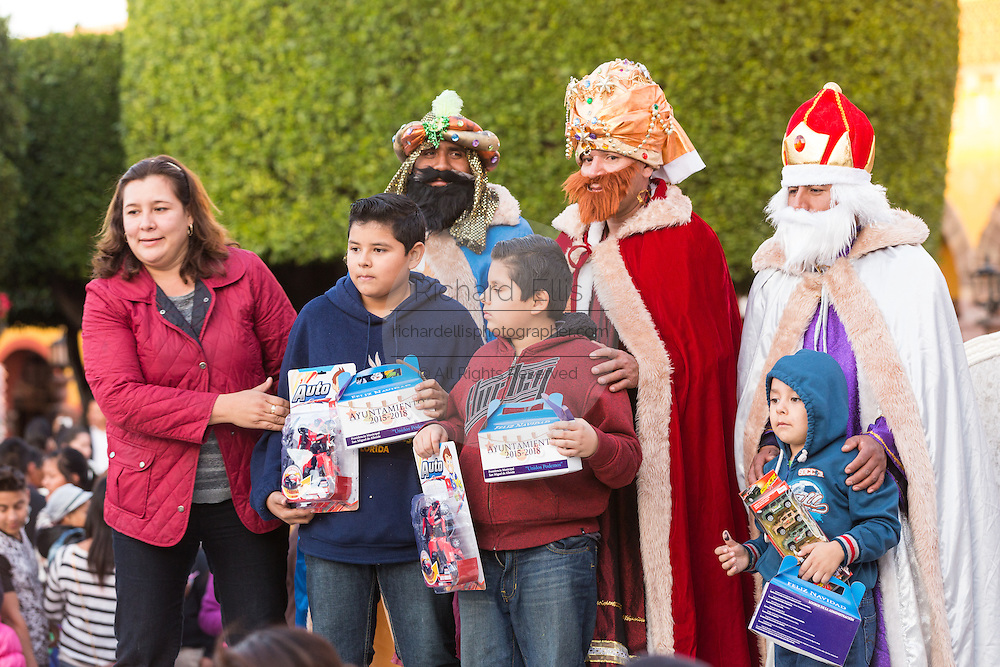 Mexican children pose with the Three Kings with there presents during El Dia de Reyes in the historic Jardin January 6, 2016 in San Miguel de Allende, Mexico. The traditional festival marks the culmination of the twelve days of Christmas and commemorates the three wise men who traveled from afar, bearing gifts for the infant baby Jesus.