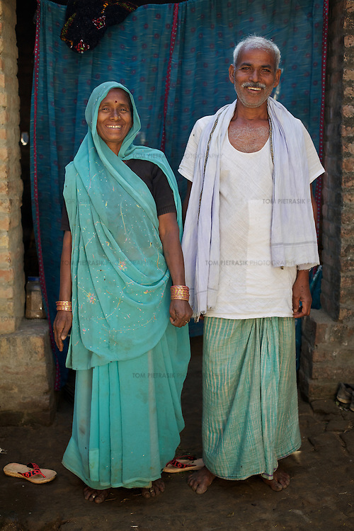 Phoola Devi and Bhonai at home in Belauhi.<br /> <br /> Phoola Devi, 48, and her husband, Bhonai are from the Yadav caste and live in Belauhi hamlet. Phoola is a member of a village SHG (Self Help Group) and has seven children. The family own 13 acres of land (though floods mean that only 5 of them arable) along with two buffalos and two cows. Phoola explains that &ldquo;Being in the SHG brings women together and since we are saving money, its very easy to access loans in the event of an emergency for example if your children are sick, you can borrow money. And there is a bond that develops among us; its very strong. We help each other and can work together.&rdquo; With training and advice from GDS, Phoola and Belauhi have been able to increase their family's wheat production from 10-12 quintals of wheat per acre to 16-18 quintals per acre. And by growing other crops like gram, maize and vegetables they have built up the capital to invest in better fertilisers, to improve their house and to pay for their daughers&rsquo; weddings.<br /> <br /> Bypassed by government subsidies that direct resources towards the needs of larger land-owners, farmers in the hamlet of Belauhi used to only harvest two crops per year and one of these crops - the monsoon Khairf rice crop - would regularly be destroyed by rains. Training and advice provided by Oxfam partners GDS (Grameen Development Services) has allowed Belauhi's farmers to harvest three - and sometimes four - crops so increasing food security and allowing some to move beyond subsistence farming and begin selling farm produce. Crop varieties that can withstand the flooding of fields in the monsoon or the intense heat of summer, including the genetically modified NDR-97 variety of rice, are more suited to farming in an unpredictable climate. New crops including pulses and oil seeds have provided residents a more balanced diet. GDS train local farmers, including women, in new agricultural techniques: irrigation and drought resistant crops. GDS has also establish