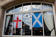 The English Cross of St. George and the Scottish Saltire flags hang together in a pub window, on 2nd October 2019, in Sutton, London, England