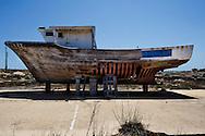 """Lampedusa, Italia - 3 luglio 2011. Un peschereccio tirato a secco e """"ridotto all'osso"""" rappresenta metaforicamente la attuale realtà dell'isola di Lampedusa dopo l'emergenza immigrati dello scorso inverno: un calo del turismo del 70%..Ph. Roberto Salomone Ag. Controluce"""