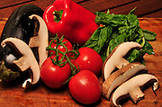 Portabella mushrooms, vine-ripened tomatoes, fresh basil, and eggplant on a cutting board.