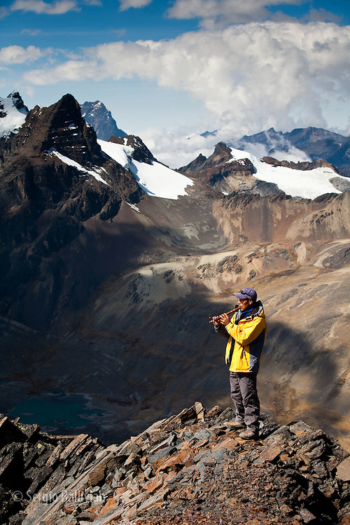 Trekking guide, Luis Mamani, plays his quena (an andean flute) with Mt. Willomen (17,923'/5463m) in the background from the summit of Pico Austria (17,385 ft / 5300 m) in Bolivia's Cordillera Real during typical winter weather.