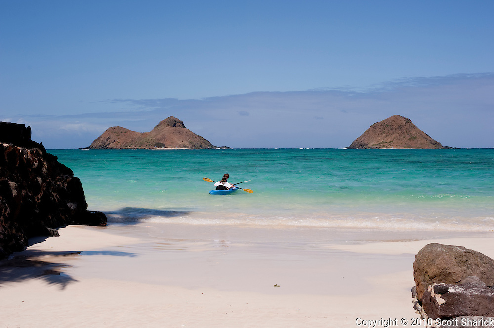 A kayaker paddles out to the Mokulua Islands from Lanikai Beach.