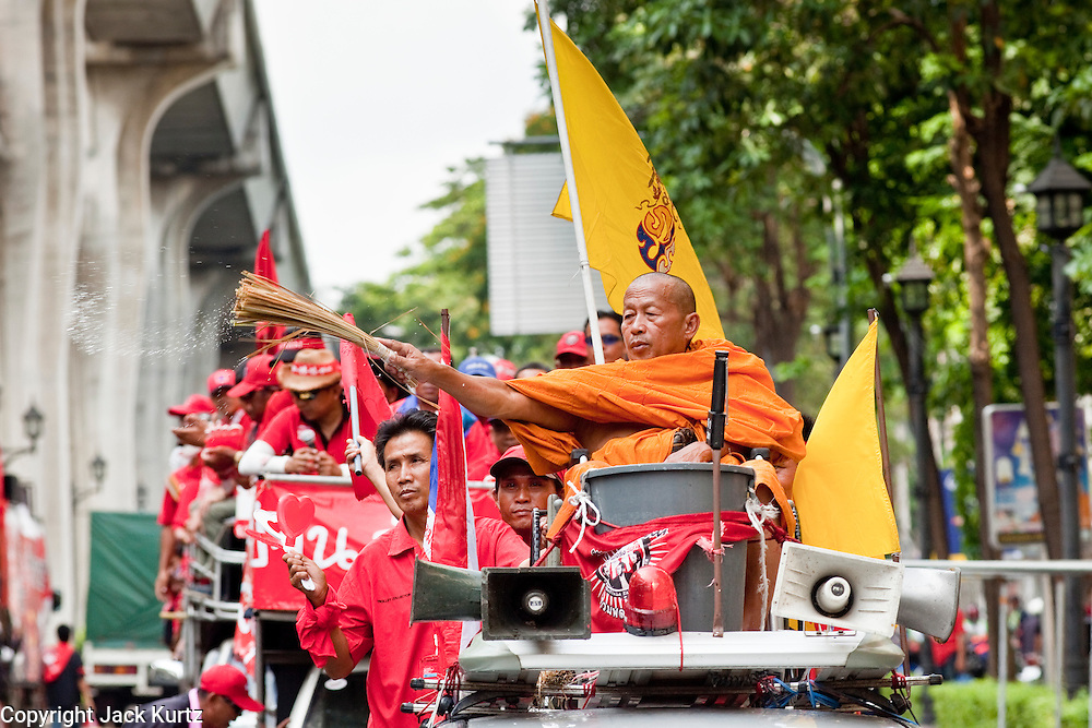 "Apr 4, 2010 - BANGKOK, THAILAND: A monk blesses Red Shirts with holy water in Bangkok, Sunday, Apr. 4. Thousands of members of the United Front of Democracy Against Dictatorship (UDD), also known as the ""Red Shirts"" and their supporters moved their anti government protests into central Bangkok Apr. 4 when they occupied Ratchaprasong intersection, the site of Bangkok's fanciest shopping malls and several 5 star hotels. The Red Shirts are demanding the resignation of current Thai Prime Minister Abhisit Vejjajiva and his government. The protest is a continuation of protests the Red Shirts have been holding across Thailand. They support former Prime Minister Thaksin Shinawatra, who was deposed in a coup in 2006 and went into exile rather than go to prison after being convicted on corruption charges. Thaksin is still enormously popular in rural Thailand. This move, away from their traditional protest site in the old part of Bangkok, has gridlocked the center of the city and closed hundreds of stores and restaurants and several religious shrines. There has not been any violence, but the government had demanded that the Red Shirts return to the old part of the city.   PHOTO BY JACK KURTZ"