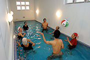 Elderly Japanese and their community caretakers play beach volleyball in an indoor pool at a senior center in the small city of Nago, Okinawa. Patrons can spend the day in a setting reminiscent of a spa, taking footbaths, enjoying deep-water massage, and lunching with friends. With their caring, community-based nursing and assistance staff, Okinawan nursing homes and senior daycare centers, both public and private, seem wondrous, vibrant and lively places. (Supporting image from the project Hungry Planet: What the World Eats)