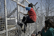 March 1, 2016 - Athens, Greece - <br /> <br /> Young boy tries to climb barbed wire fence at the Greece/Macedonia border Idomeni/Gevgelija. Thousands of migrants  are stuck at the border between Greece and Macedonia where only the Syrians and the Iraqis can pass. unfortunately after clashes with Macedonian police of 29 February, the border remains closed causing mass crowding. Some 10,000 people are now on the border, in desperate conditions. <br /> ©Exclusivepix Media
