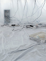 Computer and cables covered in dust sheets with paint roller in foreground
