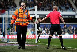 Referee Andy Davies hands over a beer bottle that had been thrown onto the pitch