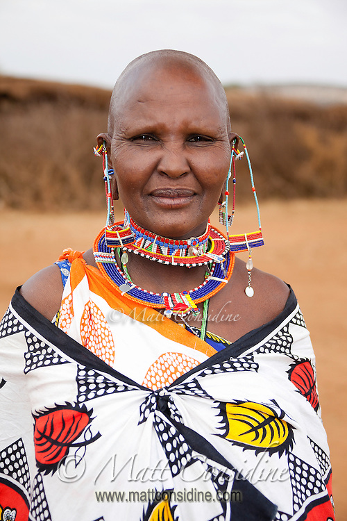 African woman from the Masai tribe in Kenya wearing traditional handcrafted beadwork earrings and necklaces and a boldly patterned cloth, Kenya, Africa (photo by Travel Photographer Matt Considine)