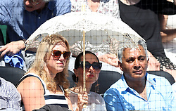 Spectators try to shield themselves from the sun during day one of the Aspall Classic at the Hurlingham Club, London.