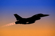 Silhouette of an Israeli Air Force F-16B Fighter jet at dusk.