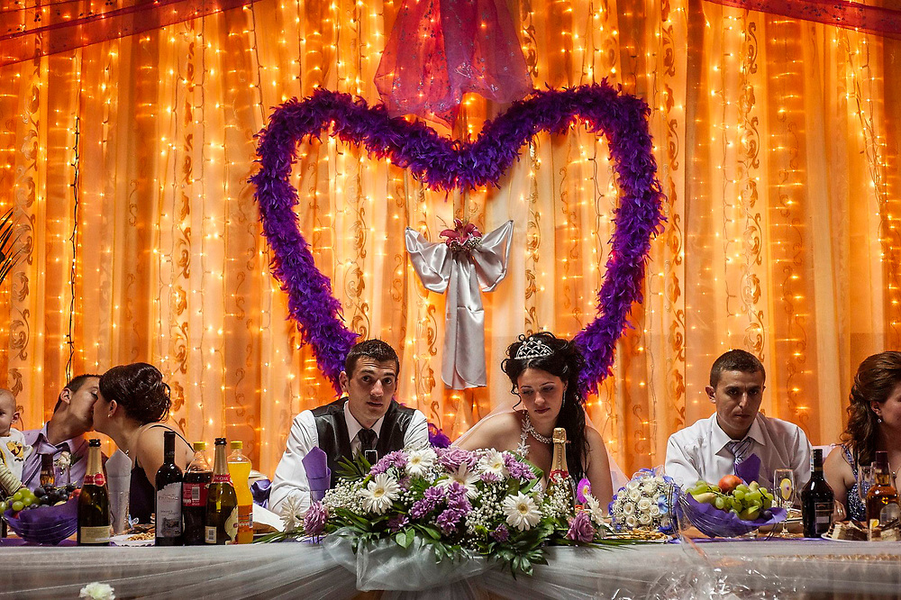 Ionut and Mia sitting at the top table at their wedding with friends and family. They both work in Paris but have come back to their village to get married.