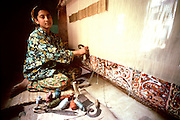 INDIA, ARTS, CRAFTS a young girl weaving a carpet on a loom  in her home in Srinagar, Kashmir