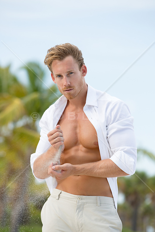 sexy man on the beach holding sand in his hands