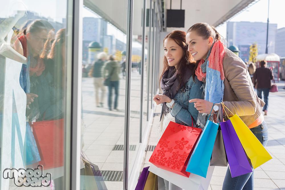 Shopaholic female friends window shopping