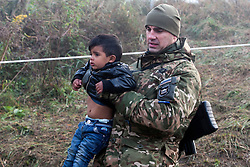 Licensed to London News Pictures. 24/10/2015. Sentilj, Slovenia. Migrants are walking to the border crossing to Spielfeld, Austria. Slovenian soldier is carrying a boy. Photo: Marko Vanovsek/LNP