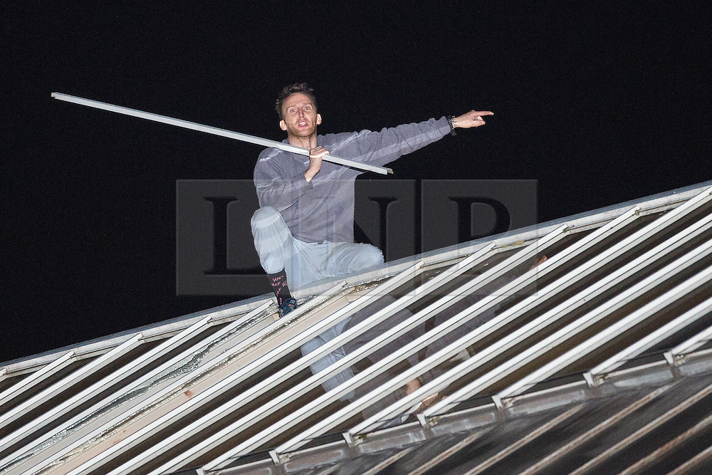 © Licensed to London News Pictures . 14/09/2015. Manchester, UK. An inmate at HMP Manchester ( Strangeways Prison ) , identified locally as STUART HORNER , shouts to watching crowds , after climbing a fence and on to the roof , in protest at conditions inside . Photo credit : Joel Goodman/LNP