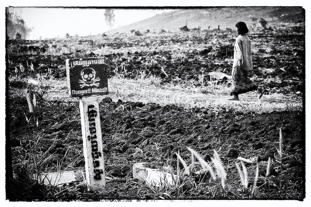 A former Khmer Rouge cadre walks past a landmine marker along the Thai-Cambodia border near Pailin.