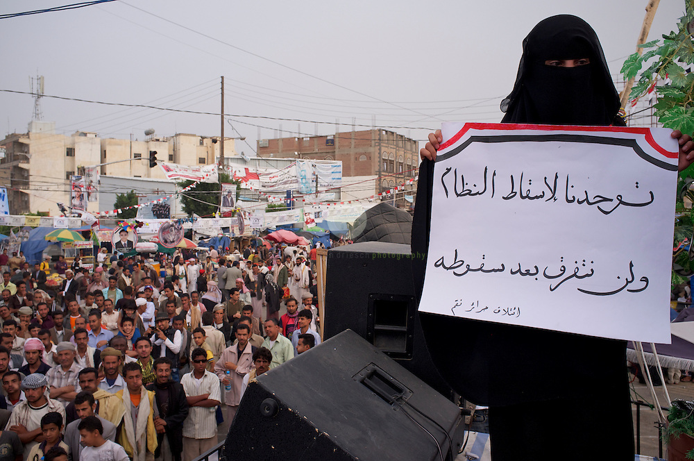 Turmoil in Yemen: ASIA, YEMEN, SANA, 20.06.2011. Anti-government protesters at Change Square in Sana, Yemen. Dances and songs are performed on stage. This womans holds a sign which says: We are here united in our fight against the regime. Our unity will not ease to exist after a change.