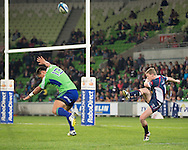 Bryce Hegarty (Rebels) kicks as Jason Emery (Highlanders) evades during the Round 17 match of the 2013 Super Rugby Championship between RaboDirect Rebels vs Highlanders at AAMI Park, Melbourne, Victoria, Australia. 12/07/0213. Photo By Lucas Wroe