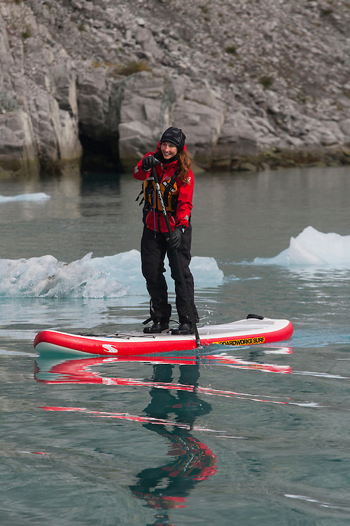 A stand up paddle boarder paddles through the ice with her reflection below. MR