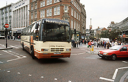 Coach turning corner in town centre,