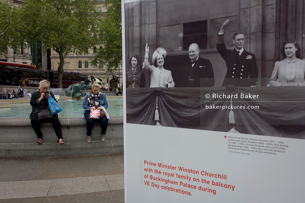 Visitors interact with an outdoor photography exhibit where on this day 70 years ago, Victory in Europe (VE) Day was celebrated by the royal family and Winston Churchill and ecstatic crowds rejoicing the end of WW2, on the streets of London and here, in Trafalgar Square.