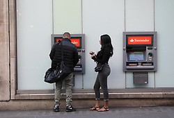 People withdraw cash from ATMs at Santander on bank branch near Oxford street, London. Picture dated: Thursday September 13, 2018. Photo credit should read: Isabel Infantes / EMPICS Entertainment.