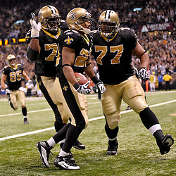 2009 November 30:  New Orleans Saints running back Pierre Thomas (23) celebrates a touchdown against the New England Patriots with teammate guard Jahri Evans (73) and guard Carl Nicks (77) during the first half at the Louisiana Superdome in New Orleans, Louisiana.