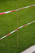 Red and white tape and cane telling pedestrians not to walk on freshly-laid lawn in the City of London.