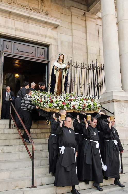 Saturday 23 March 2013 - Santander, Spain - The first procession of Holy Week 2013 makes its way across the city centre.<br /> <br /> In this image, the penitents come out of the church of San Francisco at the start of the procession, carrying a heavy float with an effigy of the Virgin Mary.