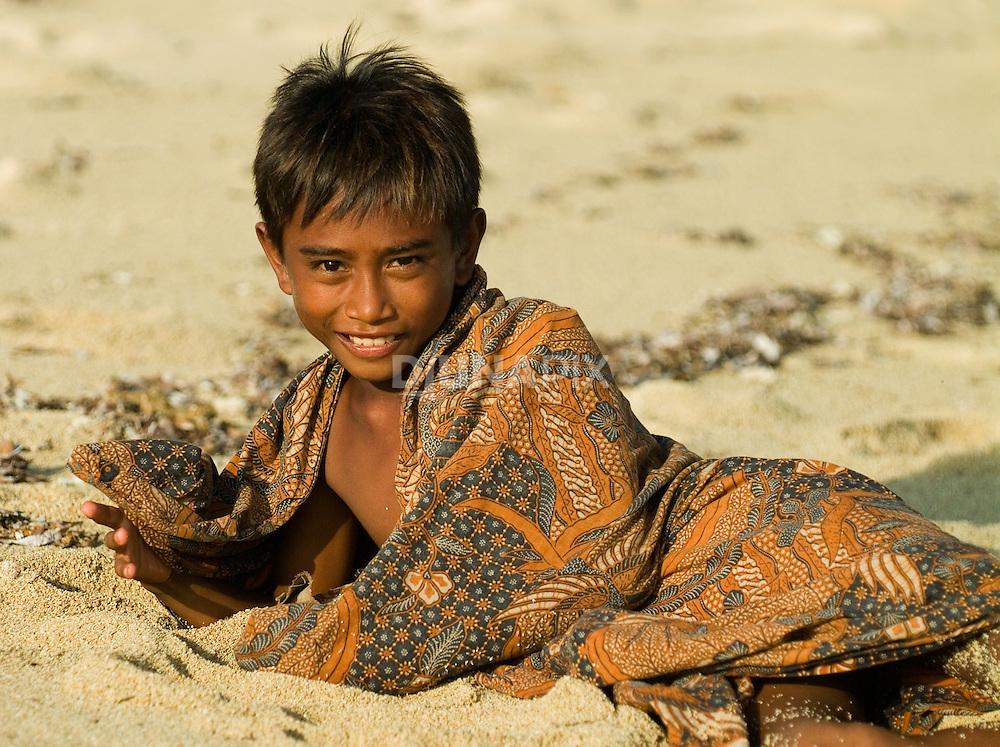 Young handsome Lombok boy models in a batik sarong, Sepi Beach, Lombok, Indonesia