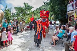 John Purpura portrays Happy Buddha to begin the New Year festivities with an eager crowd.  Alejandro Lopez and Pru Clearwater perform a Dragon dance behind him.   Nirvana Temple celebrates the Chinese New Year.  St. Thomas, USVI.  7 February 2016.  © Aisha-Zakiya Boyd
