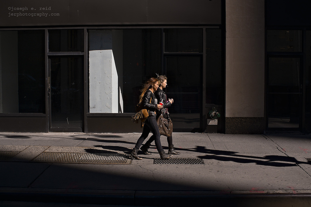 Two young women passing empty storefront