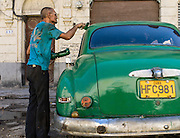 A handroller is used to paint a vintage car. Habana Vieja, Cuba.