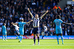 Gareth McAuley (NIR) of West Brom celebrates his sides second goal in the opening 5 minutes of the match as Emmanuel Adebayor (TOG) of Tottenham Hotspur holds his arms up in dejection - Photo mandatory by-line: Rogan Thomson/JMP - 07966 386802 - 12/04/2014 - SPORT - FOOTBALL - The Hawthorns Stadium - West Bromwich Albion v Tottenham Hotspur - Barclays Premier League.