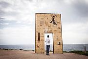 """Lampedusa, Sicilia, ott 2013. Lampedusa Island, Sicily, Italy, oct 2013. MIgrante eritreo presso il monumento la Porta d'Europa of Mimmo Paladino. Migrant at the monument """"The Europe door"""""""
