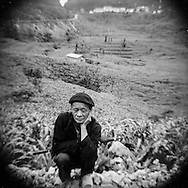 Portrait of a Vietnamese farmer man squatting along the road, Ha Giang Province, Vietnam, Southeast Asia