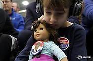 Anne-Sophie Marquis cradles her doll Clare, wearing a button supporting U.S. Republican presidential candidate Donald Trump, at a Trump campaign rally in Plymouth, New Hampshire February 7, 2016.  REUTERS/Rick Wilking - RTX25V29