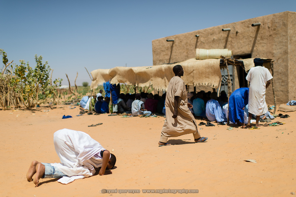 A man performing a ritual prayer on entering the mosque compound in the village of Mbera, Mauritania on 8 March 2013. Though the mosque is located in the 'village' - the original site of a refugee camp for Malians fleeing conflict in Mali in the early 1990s - it now also serves the current Mbera refugee camp, which is home to approximately 70 000 refugees fleeing the present conflict.