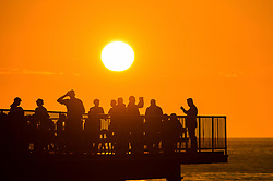 &copy; London News Pictures . 17/06/2017. Aberystwyth, UK.<br /> People drinking on the pier enjoying the warm evening as the sun begins to set over the sea  in Aberystwyth, on the Cardigan Bay coast of west Wales on has been the hottest weekend of the year so far, with more , even hotter weather forecast for tomorrow. Photo credit: Keith Morris/LNP