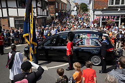 © Licensed to London News Pictures. 10/07/2020. Ditchling, UK. Crowds fill the High Street as the funeral cortege carrying the body of WWII Forces' Sweetheart Dame Vera Lynn passes through her home village of Ditchling, East Sussex. The cortege will head to a crematorium in Brighton for a private funeral. A Battle of Britain Memorial Flight flypast, consisting of a Spitfire and a Hurricane, will perform a flypast at noon. Photo credit: Peter Macdiarmid/LNP