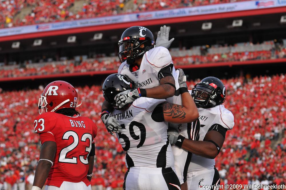 Sep 7, 2009; Piscataway, NJ, USA; Cincinnati offensive lineman Alex Hoffman (59) lifts teammate running back Isaiah Pead (23) after Pead's first half touchdown as Rutgers hosts Cincinnati in NCAA college football at Rutgers Stadium.