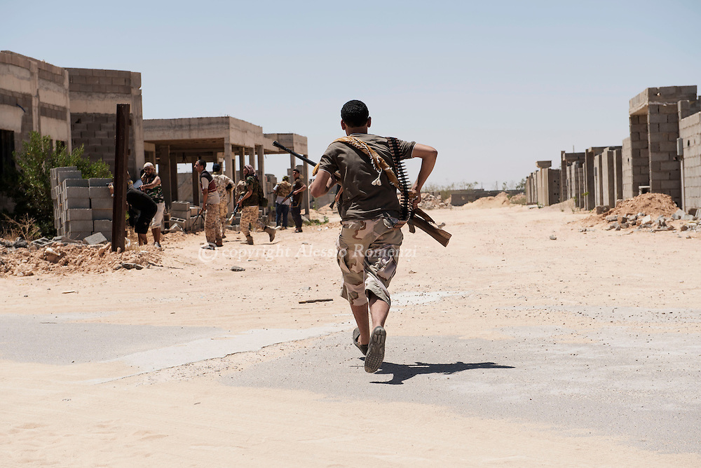 Libya: to avoid ISIS sniper fire Libya's Government of National Accord's (GNA) fighter runs to cross a road in 700 neighbourhood in Sirte still under ISIS control. Alessio Romenzi