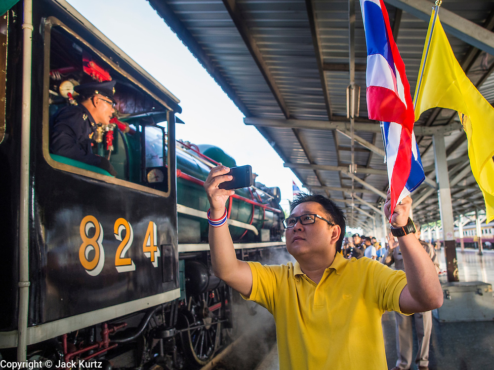 """05 DECEMBER 2013 - BANGKOK, THAILAND:  A man holding the Thai flag and the King's flag photographs a special steam engine train leaving Hua Lamphong Train Station on the 86th birthday of Bhumibol Adulyadej, the King of Thailand. Dec. 5, the King's Birthday, is a national holiday in Thailand, and is also celebrated as the country's """"Fathers' Day."""" The State Railways of Thailand put on special trains to take people to the King's """"Summer Palace"""" in the oceanside community of Hua Hin where the King granted a public audience. There were also merit making ceremonies throughout the country.  Many people wear yellow on the King's Birthday because yellow is the color associated with his reign. As of 2013, he was the longest reigning monarch in the world.          PHOTO BY JACK KURTZ"""