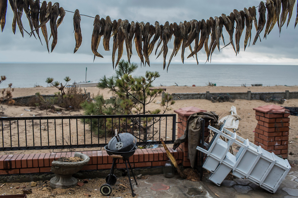 Fish are hung to dry outside a damaged vacation home occupied by Ukrainian soldiers on the coast of the Sea of Azov on Saturday, March 19, 2016 in Shyrokyne, Ukraine. The town was until recently the scene of intense fighting, but is now fully controlled by Ukrainian forces.