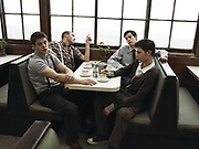 Four young men sitting in a cafe booth drinking tea.