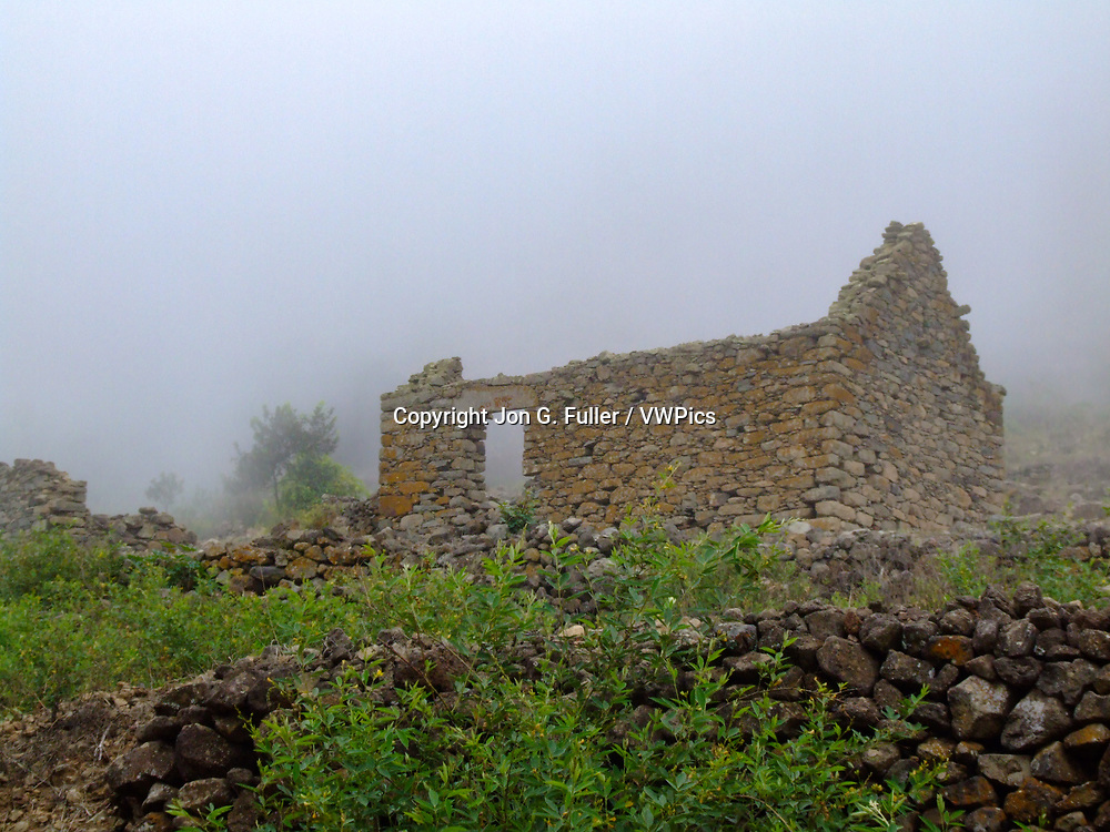 Fog envelopes the ruins of old farmhouses in the Cova de Paul Crater on Santo Antao, Republic of Cabo Verde, Africa.
