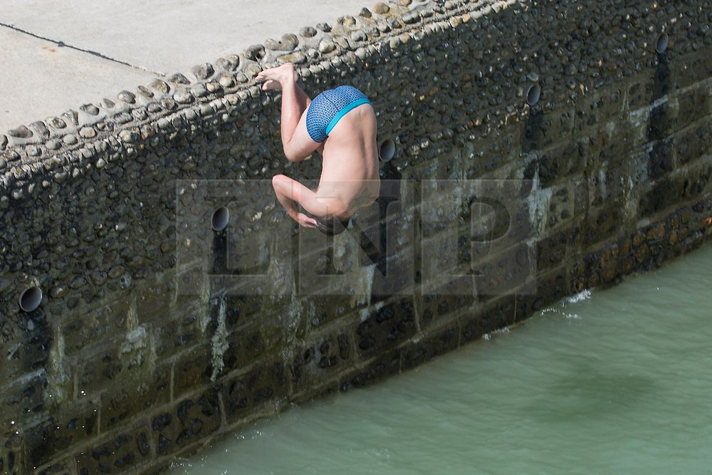 © Licensed to London News Pictures. 09/09/2017. Brighton, UK. a young man can be seen jumping of the pontoon in the sea next to the Brighton Palace Pier. Photo credit: Hugo Michiels/LNP