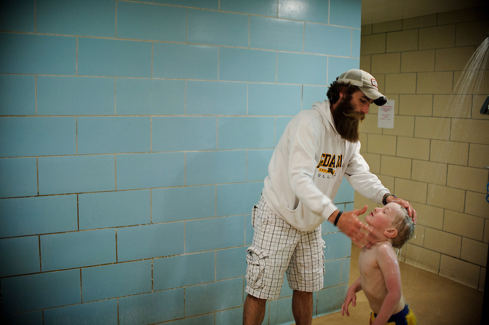 photo by Matt Roth.Tuesday, April 10, 2012..After swim lessons at McDaniel College's Harlow Pool in Westminster, Maryland Tuesday, April 10, 2012, Ron Shriver efficiently uses the locker room shower as a way to ready his children Rory, 6, out of frame, and Miles, 5, right, for bed. After showering, they put on their pajamas, so when they get home they are ready for bed. Ron will wake up at 3am the next day to study for an exam. Ron Shriver is a retired marine staff sergeant. He is also the first in his family to attend college, thanks to the New G.I. Bill.Ron Shriver is a retired marine staff sergeant. He is also the first in his family to attend college, thanks to the New G.I. Bill. His wife, a fellow retired Marine, is finishing up graduate school in Alaska. After Ron gets his undergraduate degree from McDaniel College in May, he plans to drive to Alaska with is two children Rory, 6, and Miles, 5. For the move Ron got rid of most of his family's belongings, and after his lease was up, he and his children moved back into his parent's farmhouse.